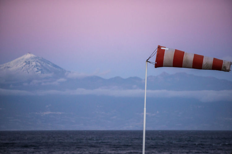 Windsock by sea against sky during sunset