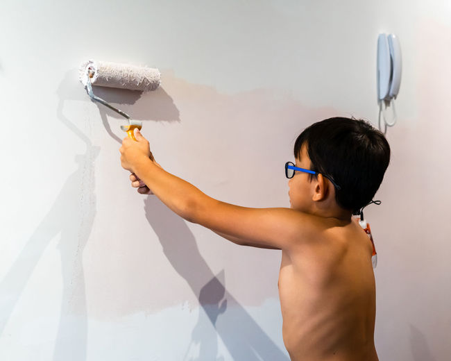 Side view of shirtless boy standing against wall