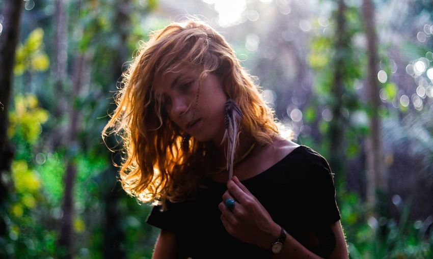 Thoughtful Woman Holding Hair Against Trees