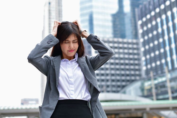 Stressed businesswoman standing in city