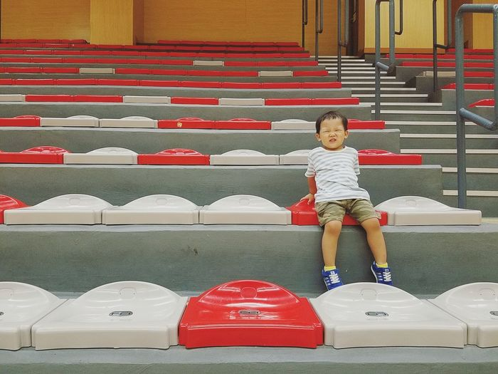 Boy Boy Smiling Sportsground Red White Child Full Length Childhood Multi Colored Red Sitting Front View Steps And Staircases Stairway