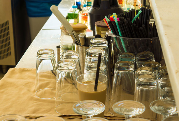 Drinking glass and jar by straws on table