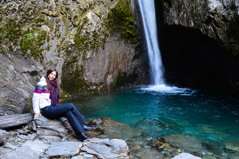 Portrait of woman sitting on rock against waterfall