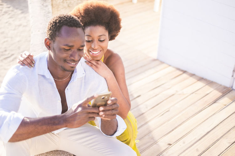 beautiful couple of black race african models use the smartphone together in friendship smiling and enjoying the contents. Sitting Sunlight Adult African Ethnicity Bonding Boyfriend Couple - Relationship Day Emotion Friendship Girlfriend Happiness Leisure Activity Love Men Positive Emotion Relaxation Smiling Three Quarter Length Togetherness Two People Women Young Adult Young Men Young Women