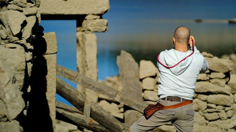Rear View Of Man Standing By Stone Wall During Sunny Day