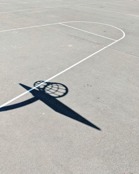 Shadow of basketball hoop on ground