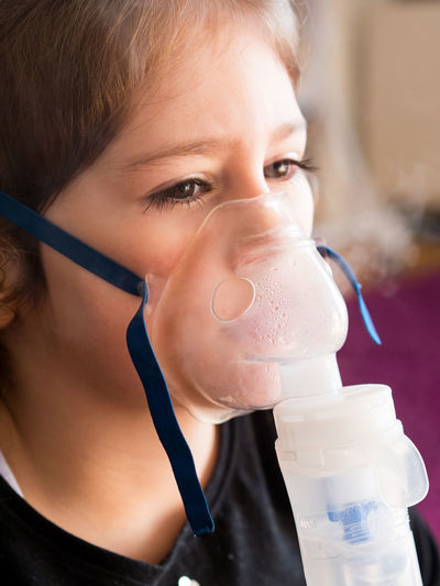 Small caucasian girl inhaling with oxygen inhalator at home Girl Kid Child Childhood Ill Small Little Cute Caucasian Inhaler Inhaling Inhalation Oxygen Mask Health Medicine Bronchitis Flu Home Close Up Indoors  Asthma Asthmatic Medical Treatment Allergy Patient Care Breath Headshot