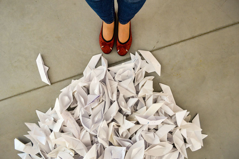 Low section of woman standing by white paper boats on floor