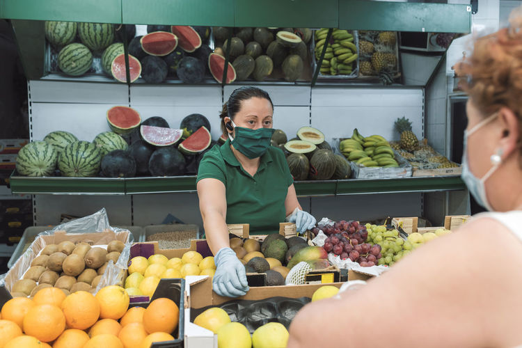 Midsection of woman with vegetables for sale at market stall