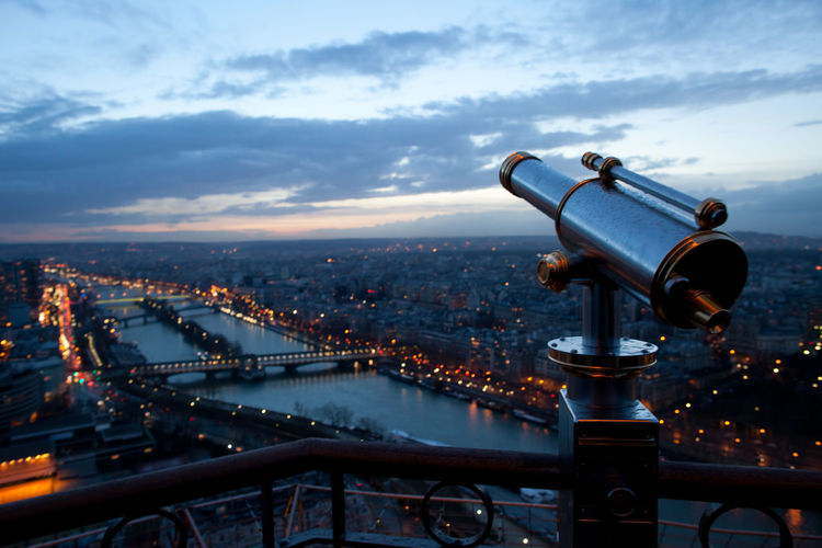 Close-up of hand-held telescope against cityscape and cloudy sky