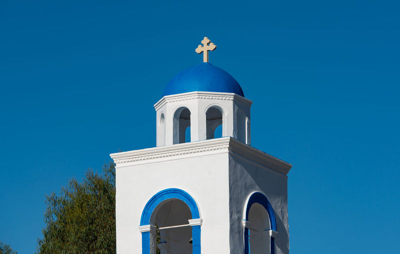 Zia and a blue white village church in front of the turkish mainland in the north on the island kos