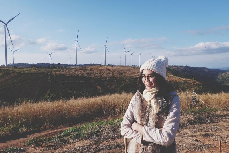 Woman wearing warm clothing while standing against windmills on mountain