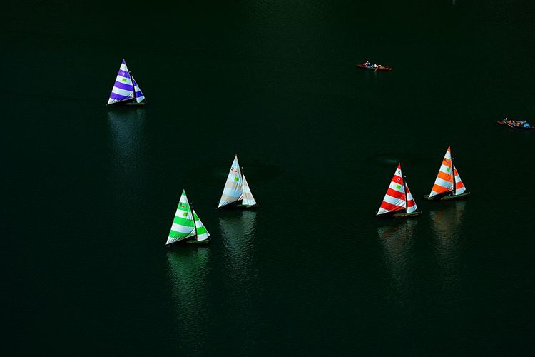 Multi colored flag on boat in lake