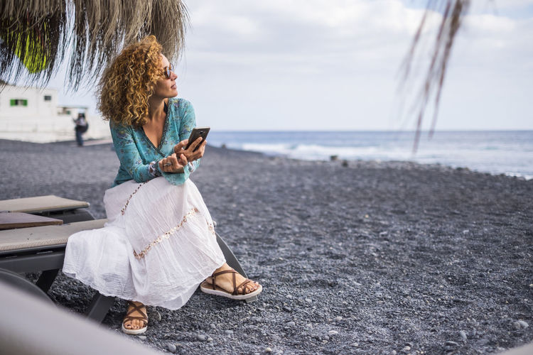 nice caucasian lady sitting on a seat at the black volcanic beach looking at the ocean and waves while check the smartphone with internet Canary Islands Adult Beach Beautiful Woman Casual Clothing Connect Curly Hair Day Full Length Leisure Activity Lifestyles Looking Ocean One Person Outdoors Real People Sitting Smiling Tenerife Transportation Using Mobile Phone Water Wireless Technology Women Young Women