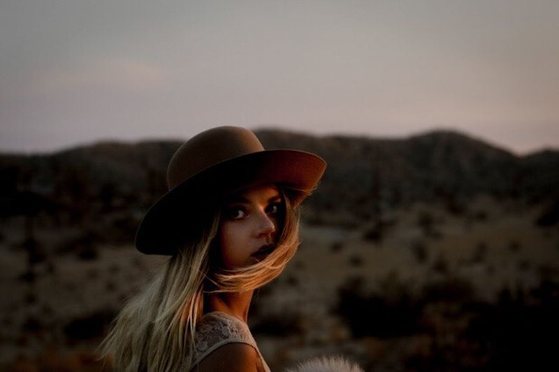 Portrait of young woman wearing hat against sky during sunset