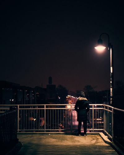 Rear view of man standing on illuminated street light at night