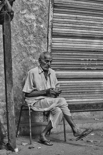 Full length of man sitting against wall