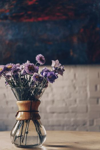 Close-up of flower pot on table against wall