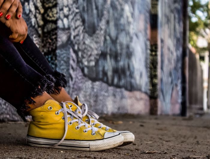 Low Section Of Woman Wearing Yellow Canvas Shoes On Footpath