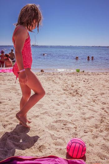 Girl walking at beach against clear blue sky
