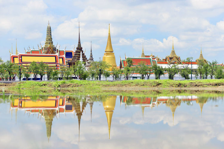Reflection of Wat Phra Kaew - The Temple of Emerald Buddha in Bangkok, Thailand Architecture Bangkok Built Structure Cloud Cloud - Sky Cloudy Day Façade Grass Nature No People Outdoors Place Of Worship Reflection Sky Standing Water Temple Temple - Building Tourism Travel Destinations Tree Wat Phra Kaew