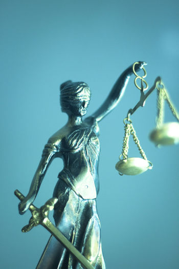 Close-up of lady justice against turquoise background