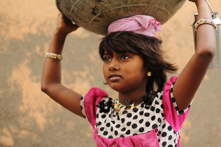 Close-up of girl carrying container on head against wall