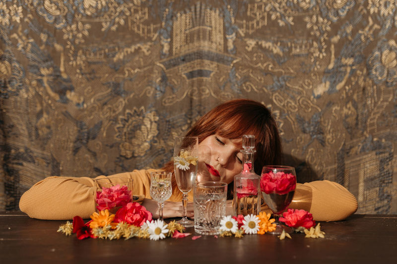 Portrait of woman drinking glass with flowers