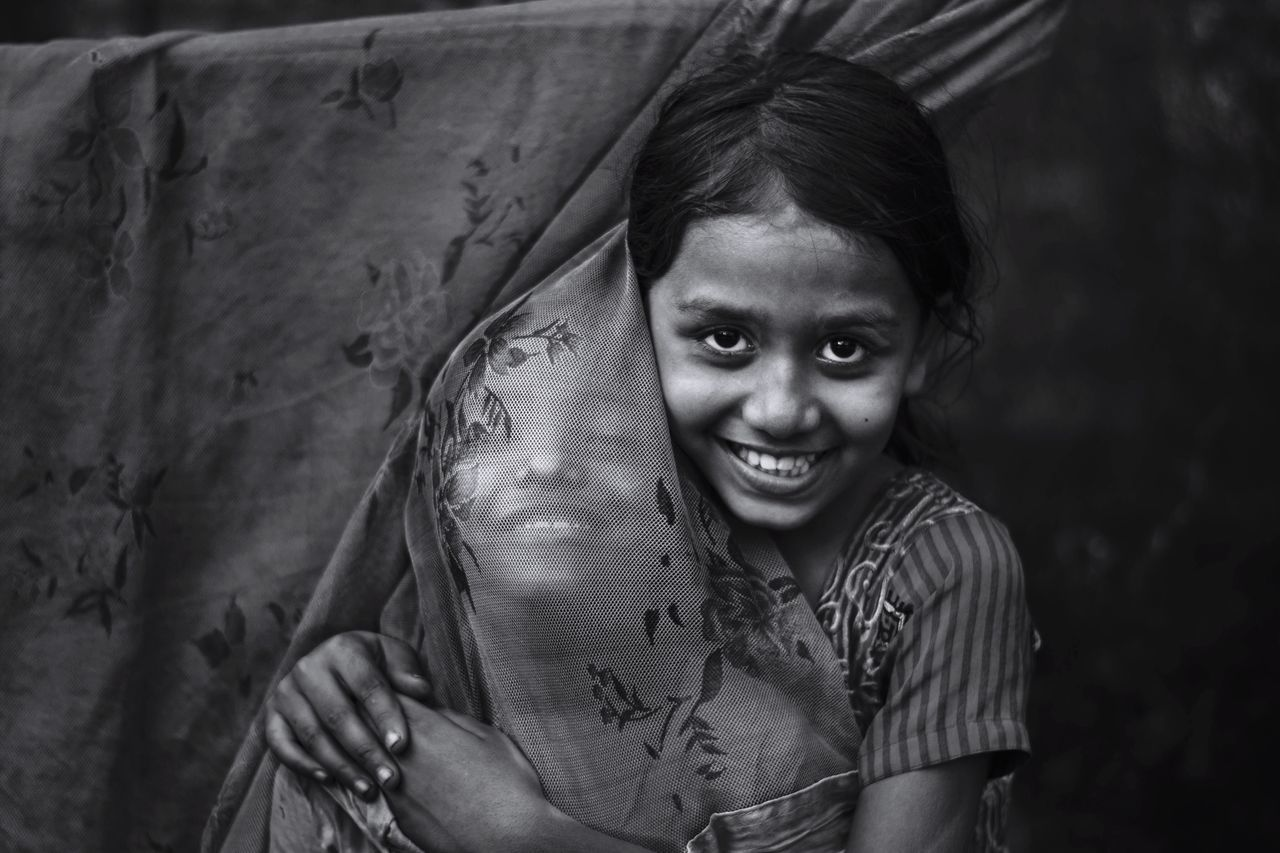 Portrait of smiling girl with friend by curtain