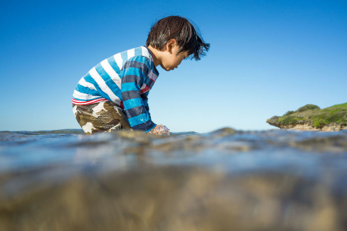 Beach Beauty In Nature Blue Boys Casual Clothing Childhood Clear Sky Day Dramatic Angles Elementary Age Innocence Nature Non-urban Scene Playing With Water Preschool Age Scenics Selective Focus Standing Summer Sunset Surface Level Toddlerlife Vacations Water Break The Mold.