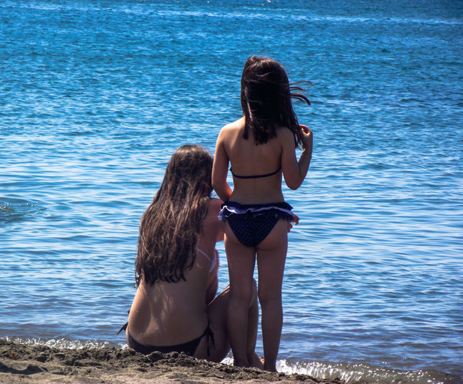 Rear view of mother and daughter on shore at beach