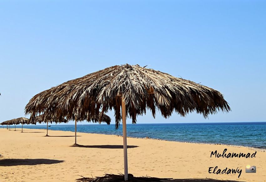 Beach Sea Sand Beach Umbrella Clear Sky Horizon Over Water Shore Water Summer Nature Beauty In Nature Tranquility Thatched Roof Tranquil Scene Vacations Protection Blue Outdoors Scenics Day Sokhabeach Wood - Material Sokhna , Egypt