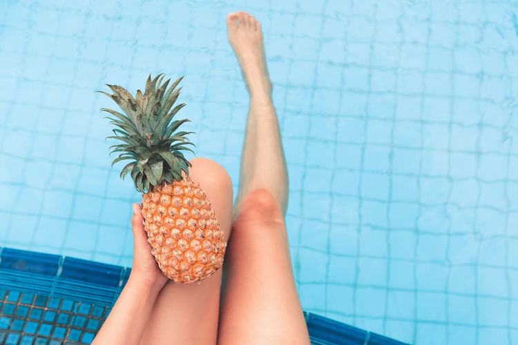Low Section Of Woman Holding Pineapple While Sitting At Poolside