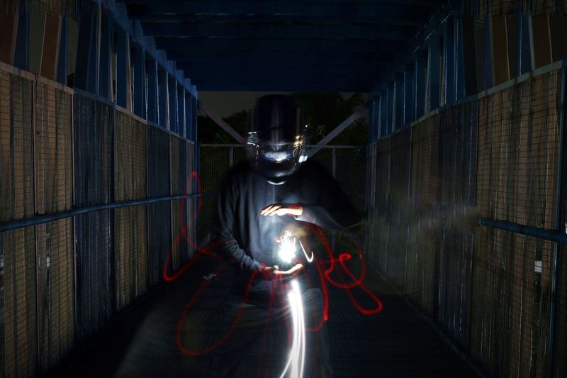 Worker with light painting in darkroom