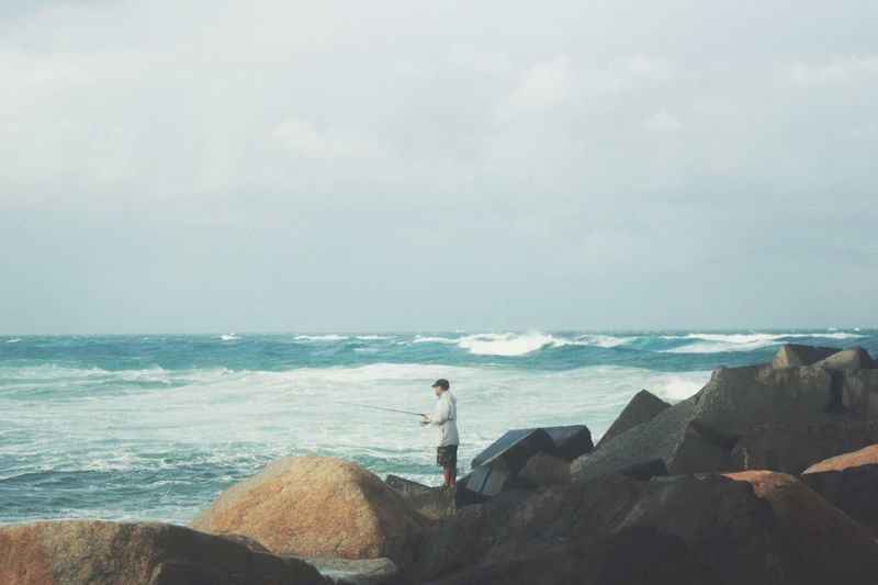 Side view of man on rock fishing in sea