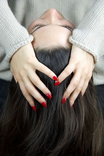 High Angle View Of Young Woman With Hands In Hair