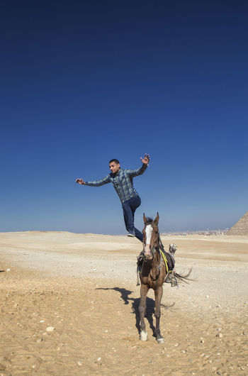 Full Length Of Mid Adult Man Jumping From Horse On Sand Against Clear Blue Sky During Sunny Day