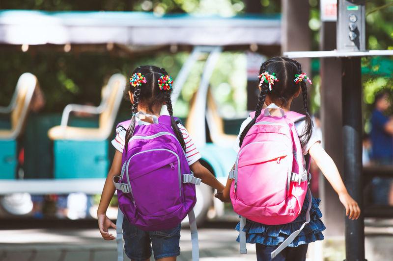 Rear View Of Schoolgirls Carrying Backpacks While Walking On Street