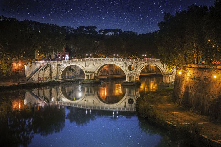 Arch Bridge Over Canal Against Sky At Night