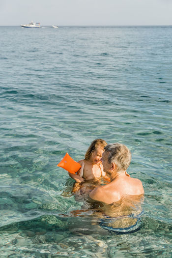 High angle view of father and granddaughter swimming in sea