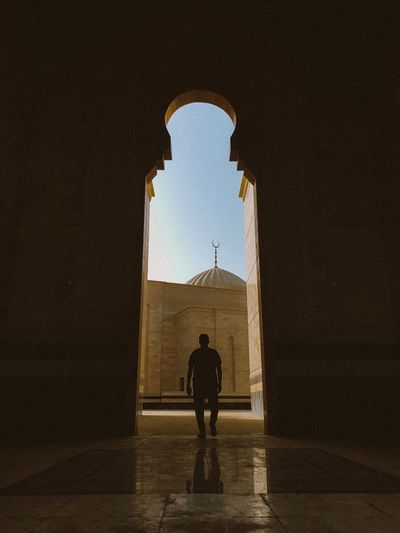 Rear view of silhouette man standing in mosque