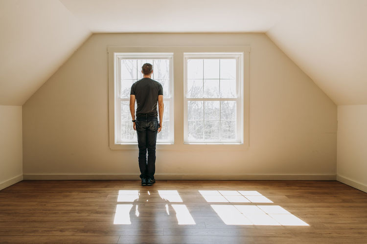 Rear view of man standing by window at home