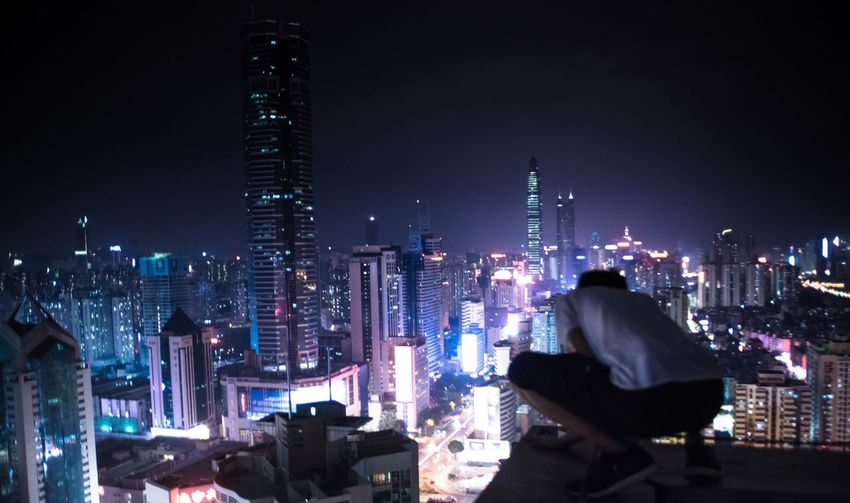 Rear view of man with illuminated cityscape in background