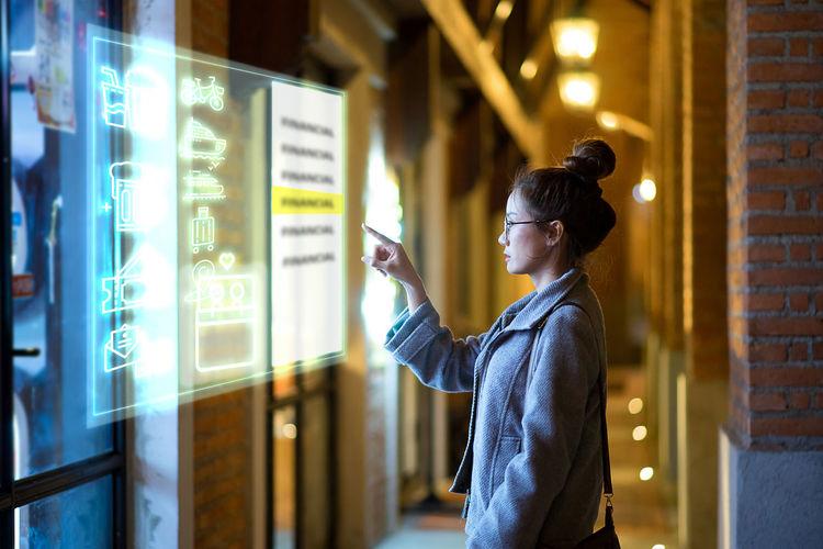 Woman Pointing At Illuminated Display In Corridor
