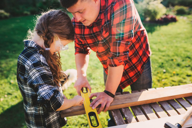 father teaching kid daughter to use tools. Girl helping dad with building work outdoor in summer, country house on background Men Two People Real People Leisure Activity Child Males  Lifestyles Togetherness Wood - Material People Childhood Checked Pattern Outdoors Plaid Shirt  Father Fatherhood Moments Father And Daughter Dad Daddy's Girl Tools Repair Teaching Hobby Family