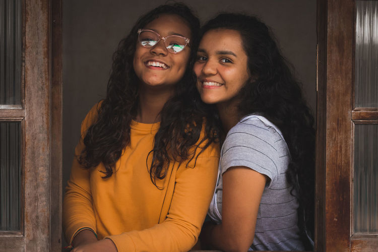 Portrait of smiling sisters by window