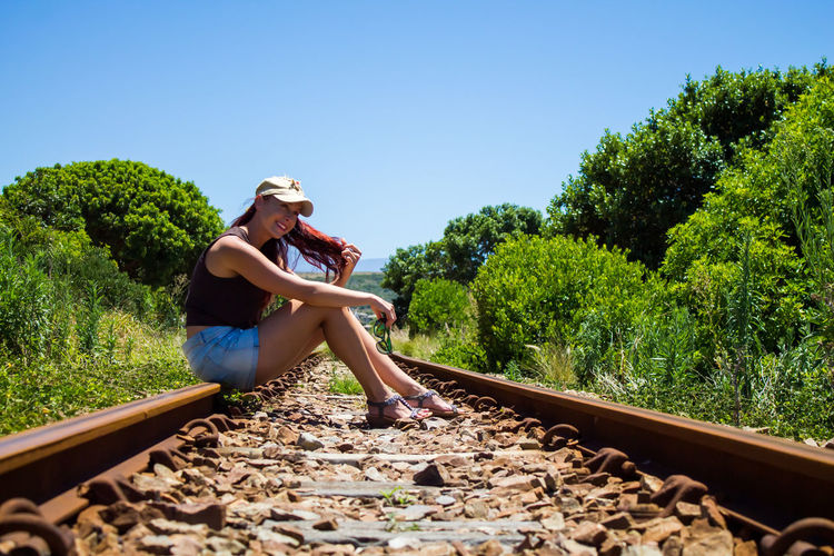Full length of woman on railroad track against clear sky