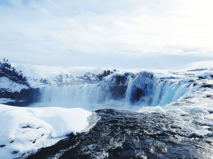Scenic view of waterfall against cloudy sky during winter