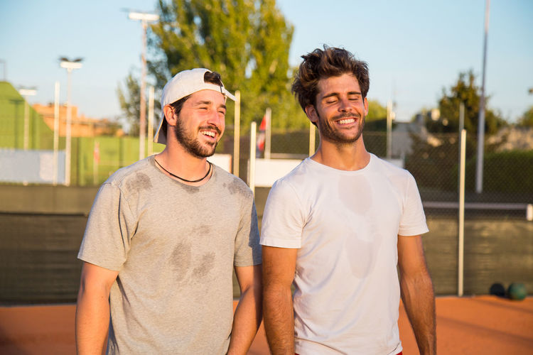 Smiling Male Friends Standing On Field During Sunny Day
