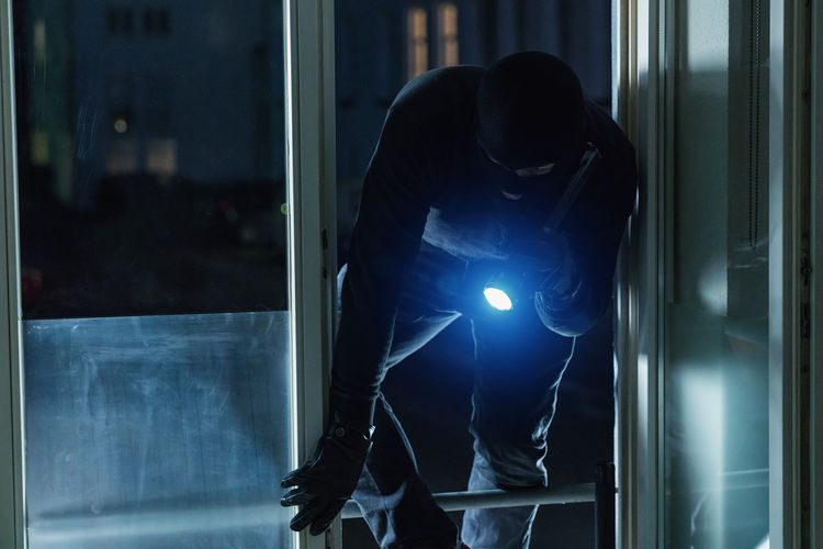 Burglar climbing in to a Victims house at night Adult Breaking Climb Crime Theft Victim Alarm Bank Burglar Burglary Criminal Flashlight Gangster Gloves Holding Housebreaker Justice Mask One Person People Real People Robber Standing Terrorism Window